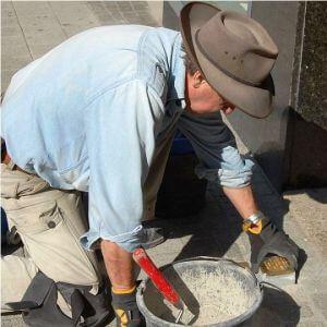 Gunter Demnig mentre posa una pietra d'inciampo